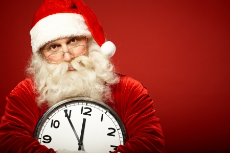 natale: Photo of Santa holding clock showing five minutes to midnight Stock Photo