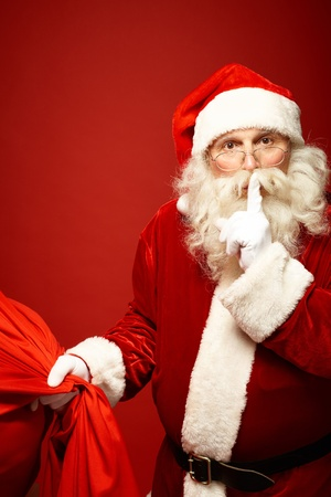 Portrait of Santa Claus with huge red sack keeping forefinger by his mouth and looking at camera photo