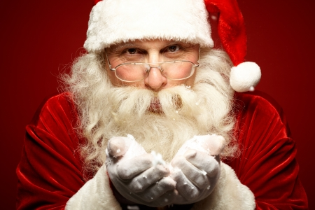 Photo of kind Santa Claus with snow in hands looking at camera photo