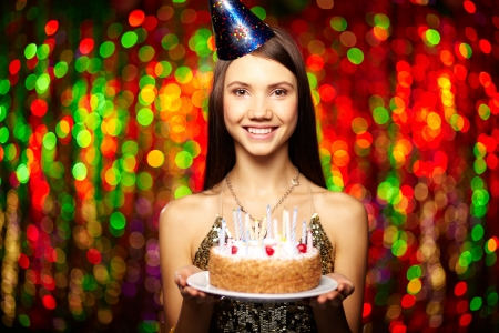 Portrait of joyful girl holding birthday cake and looking at camera at party photo