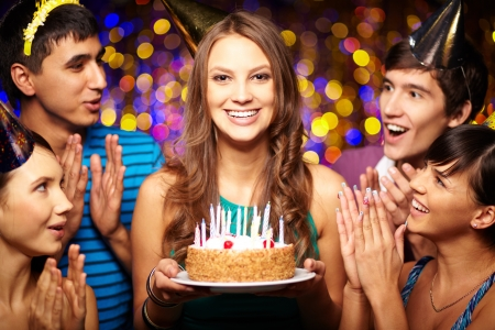 Portrait of joyful girl holding birthday cake surrounded by friends at party Stock Photo - 16333823