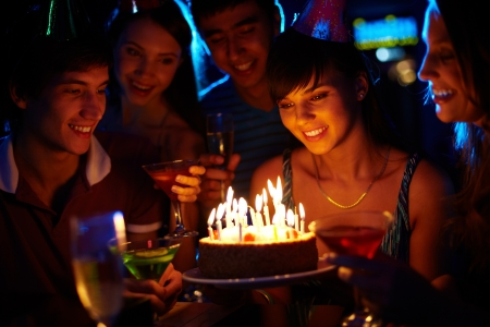 birthday candle: Portrait of joyful girl looking at birthday cake surrounded by friends at party