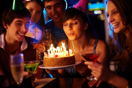 woman blowing: Portrait of charming girl blowing on candles on birthday cake surrounded by friends at party