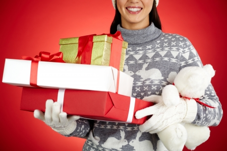 Close-up of happy girl with stack of giftboxes and white teddy photo