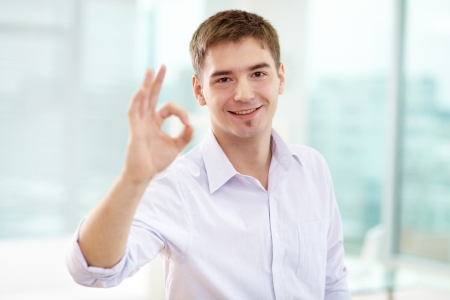 ok sign: Portrait of smiling businessman showing sign of ok and looking at camera