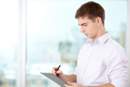 making notes: Portrait of young businessman making notes Stock Photo