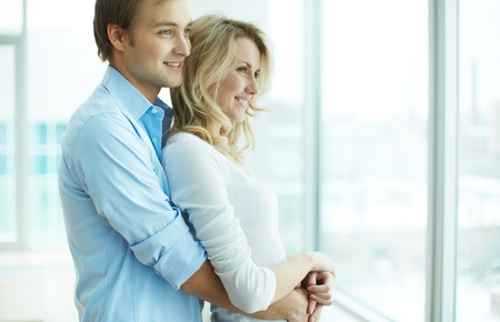 pareja abrazada: Imagen de hombre joven abraza a su novia y ambos mirando por la ventana