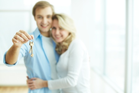 hand holding house: Image of young happy couple embracing while man showing key from new flat