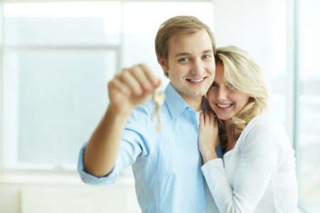 home loans: Immagine di giovane coppia felice che abbraccia, mentre l'uomo che mostra chiave dal nuovo appartamento Archivio Fotografico