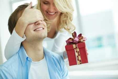 eyes closing: Image of young female with giftbox closing her boyfriend eyes to make a surprise for him Stock Photo