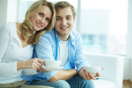 home comfort: Image of young guy and his girlfriend looking at camera while having tea