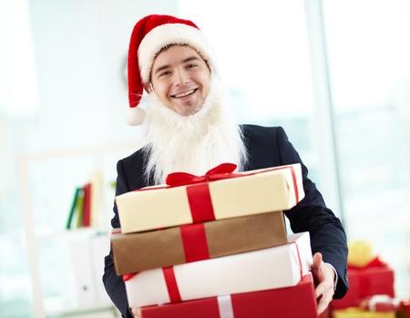 generoso: Imagen de hombre de negocios feliz en Santa gorra y barba sosteniendo stak de regalos y mirando la cámara en el cargo