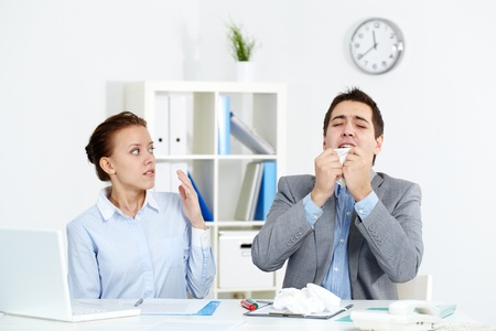 cold virus: Image of businessman sneezing while his partner looking at him with anxiety in office