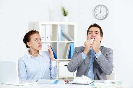 sneezing: Immagine di starnuti uomo d'affari, mentre il suo compagno che lo guardava con ansia in ufficio Archivio Fotografico