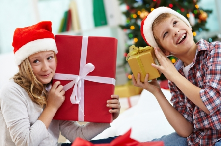 and guessing: Portrait of happy siblings holding giftboxes and guessing what is inside on Christmas evening