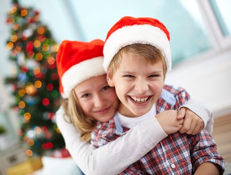 two year: Portrait of happy boy laughing in his sister embrace on Christmas evening