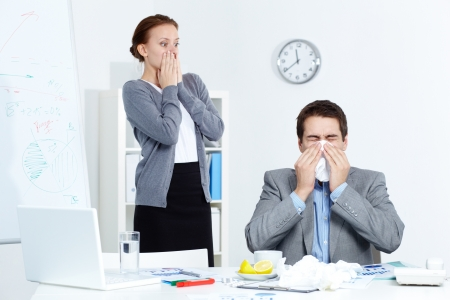 catarrh: Image of businessman sneezing while his partner looking at him with fright in office