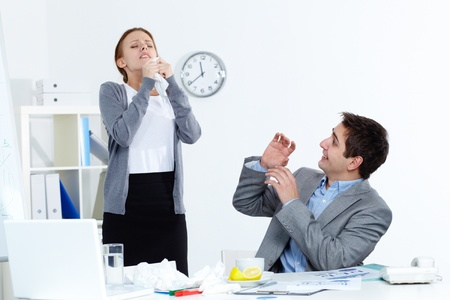 Image of sick businesswoman sneezing while her partner looking at her with anxiety in office  photo