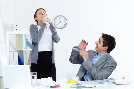 sneezing: Immagine di starnuti imprenditrice ammalato mentre il suo compagno la guardava con ansia in ufficio
