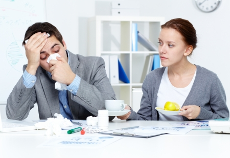 resfriado: Imagen de hombre de negocios enfermo y su secretario d�ndole una taza de t� y lim�n en el cargo