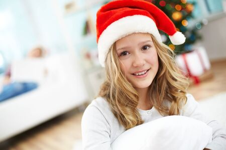 Portrait of cheerful girl in Santa cap looking at camera on Christmas evening photo