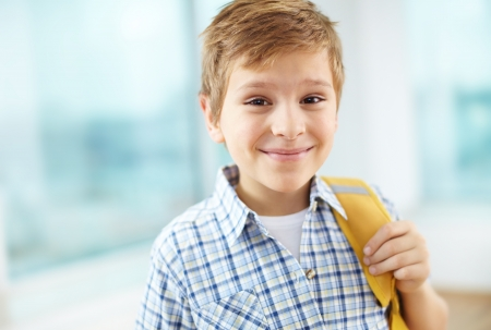 Portrait of cheerful schoolboy with backpack looking at camera photo