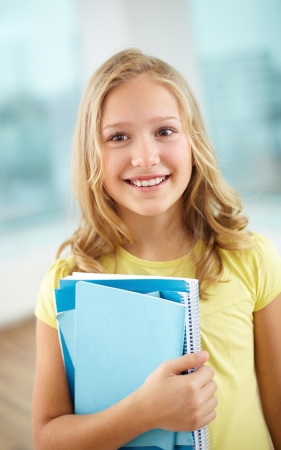 pretty smile: Portrait of cheerful schoolgirl with copybooks looking at camera Stock Photo
