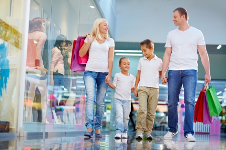 go inside: Portrait of family with paperbags walking in the mall Stock Photo