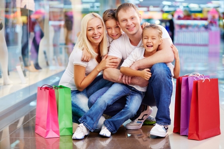 ni�os de compras: Retrato de familia feliz con bolsas de papel mirando a la c�mara en el centro comercial Foto de archivo
