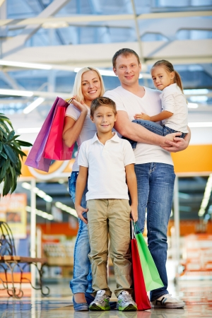 paperbags: Portrait of modern family with paperbags looking at camera in the mall Stock Photo