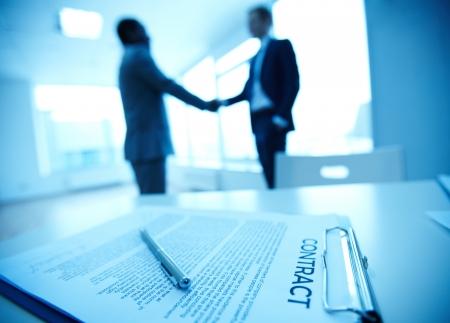Beeld van het bedrijfsleven contract op de achtergrond van twee medewerkers handshaking