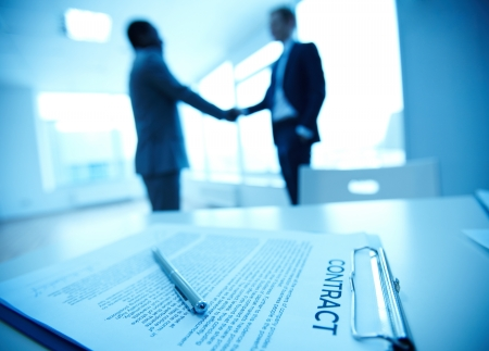 Image of business contract on background of two employees handshaking photo