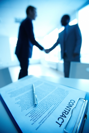 consensus: Image of business contract on background of two employees handshaking