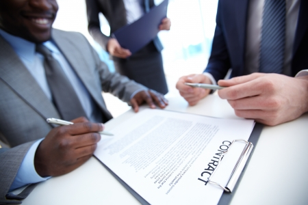 consensus: Image of businessman signing contract with two employees near by
