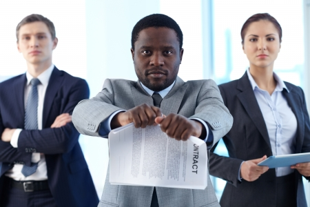 termination: Portrait of African businessman tearing contract while looking at camera with two partners on background