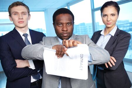 termination: Portrait of African businessman tearing contract while looking at camera with two partners near by