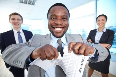 Portrait of happy African businessman tearing contract while looking at camera with two partners near by photo
