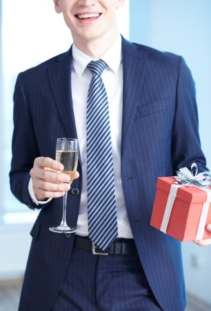Close-up of businessman in suit holding flute of champagne and giftbox photo