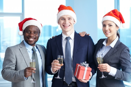 Three business partners in Santa caps holding champagne and wishing you merry Christmas photo