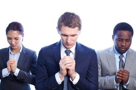 african worship: Three business partners praying with their eyes closed Stock Photo