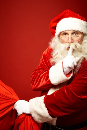 xmass: Portrait of Santa Claus with huge red sack keeping forefinger by his mouth and looking at camera Stock Photo