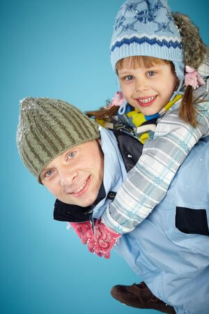 Happy father giving piggyback to his daughter and both looking at camera with smiles photo