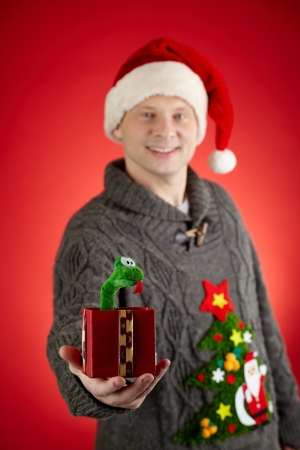 Portrait of happy man in Santa cap showing toy snake in open giftbox Stock Photo - 16499229