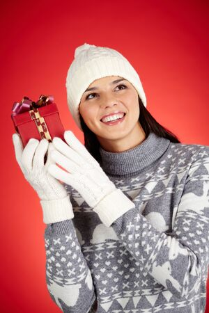 Portrait of happy girl in winterwear holding giftbox by her ear Stock Photo - 16499289