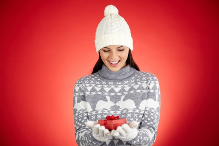 Portrait of happy girl in winterwear holding giftbox on her palms and looking at it with astonishment Stock Photo - 16499236