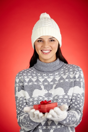 Portrait of happy girl in winterwear holding small red giftbox and looking at camera Stock Photo - 16499279