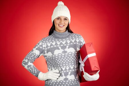 Portrait of happy girl in winterwear holding red giftbox and looking at camera Stock Photo - 16499280