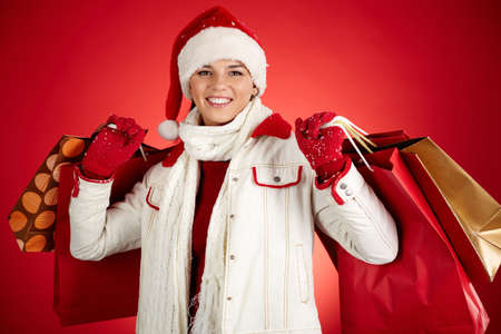 winterwear: Portrait of happy girl in winterwear holding paper bags and looking at camera