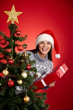 Portrait of happy girl in Santa cap holding red giftbox and looking at camera out of decorated firtree Stock Photo - 16499238
