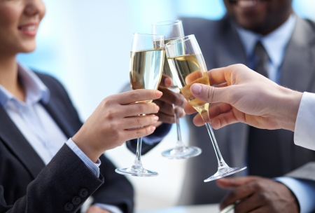 winning business woman: Close-up of business partners hands cheering up with flutes of golden champagne Stock Photo